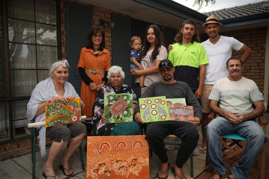 An elderly woman sits with her family who are holding up traditional Indigenous dot paintings.