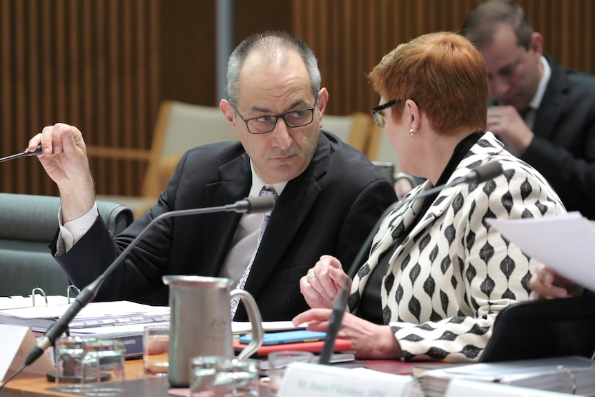 Mike Pezzullo covers his microphone while talking to Marise Payne at a table