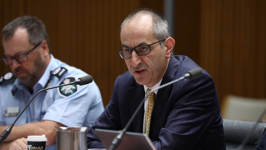 Michael Pezzullo looks towards senators out of shot as he gives evidence with an AFP officer sitting next to him