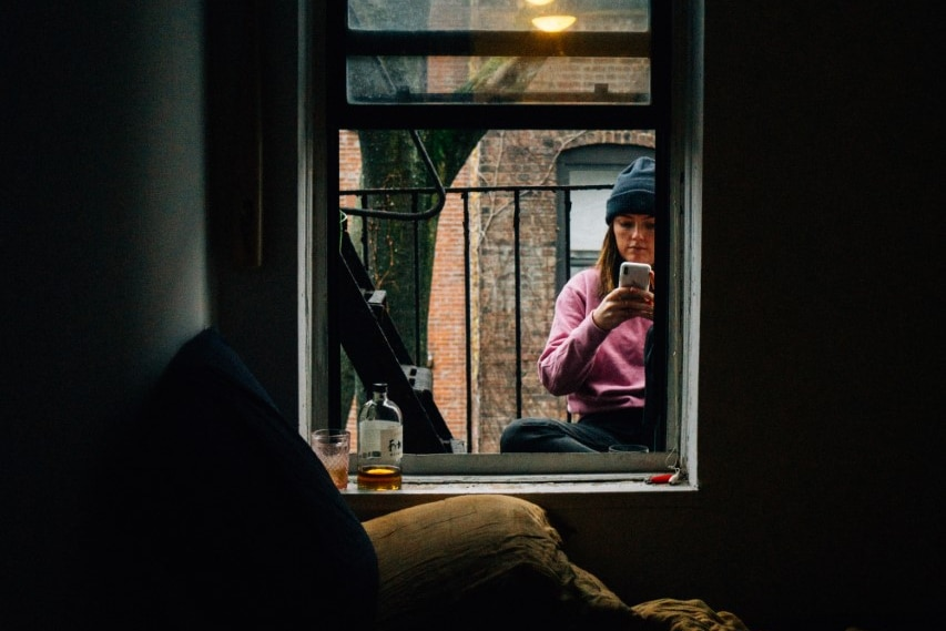 A woman sits outside the window of a small dark apartment