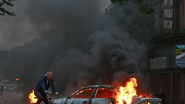 A man cycles past a burning car after Loyalist protesters attacked the police with bricks and bottles